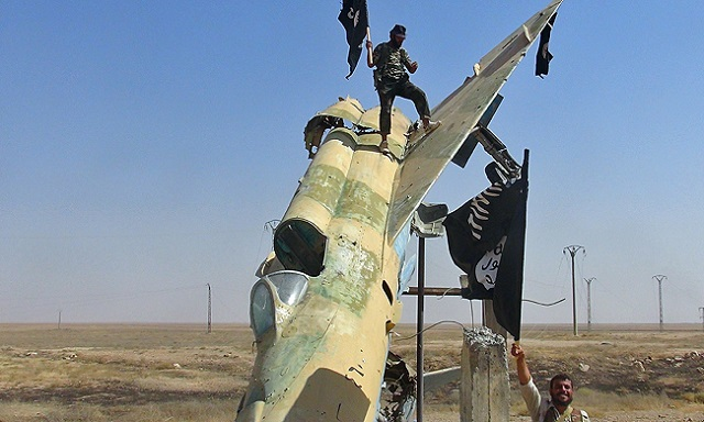 Isis fighters wave the group's flag from what is thought to a damaged a Syrian air force jet